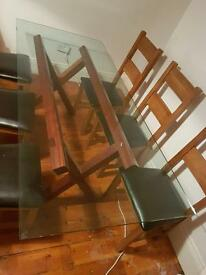 Dining table with glass top. Sits 6 to 8.