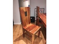 A solid oak wood table with four chairs
