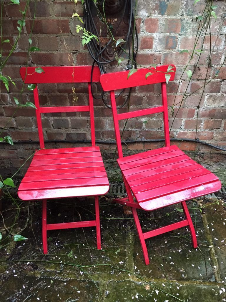 Two red metal folding patio chairs camden town