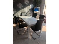 Harvey's high gloss white solid table and black leather chairs.