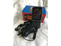 Nokia 100 with charger and unused headphones