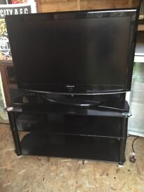 Large black tv stand with chrome pillars