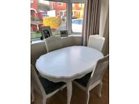 Large wooden extending dining table and four matching chairs