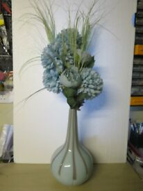 LARGE TURQUOISE BUD VASE IN PORCELAIN WITH ARTIFICIAL FLOWERS.
