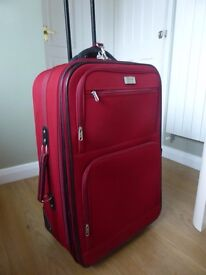 Large red suitcase on wheels, expandable, with pockets, excellent condition, used couple of times