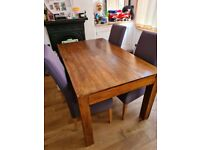 Hardwood dining table with 4 white leather chairs and purple fabric covers
