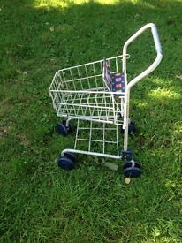 Toy shopping trolley with seat for doll