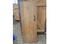 Oak planked and braced door with traditional black iron door latch