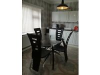Glass oval dinning table and four chairs