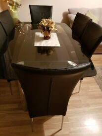 Chrome and black dining table and six leather chairs