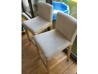 Two cream bar stools with backrests