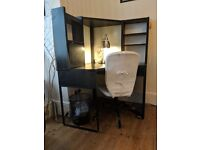 Black ikea corner desk and white padded office chair.