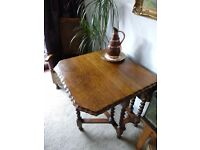 Antique oak gate leg table with barley twist legs and scalloped edge.