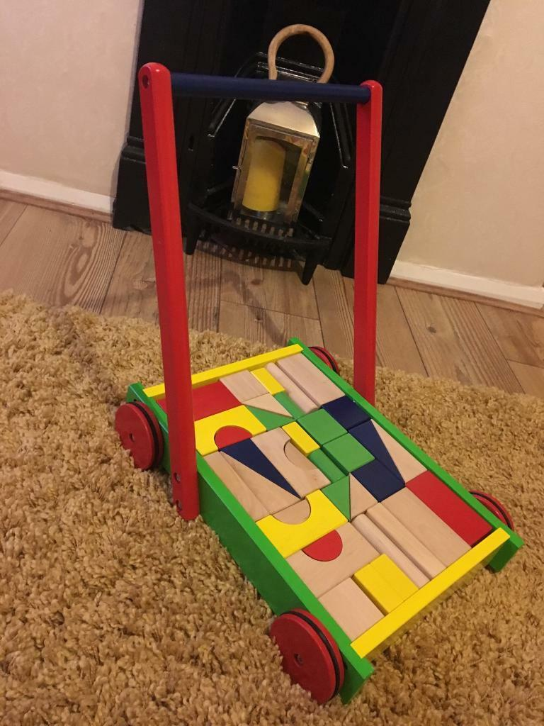 Wooden baby walker with bricks.