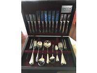 Stainless steel cutlery set in dark wood display case