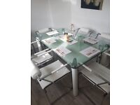 Glass dining room table and 6 chairs for sale.