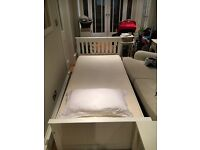 Single white wooden bed with storage and mattress plus other furniture