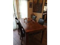 Dark solid wood dining table and 4 brown leather chairs