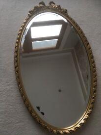 Ornate oval antique bevelled mirror