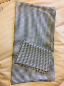 White company cot bed duvet cover and pillowcase in blue gingham design.