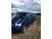 VW T5 Panel Van with a Rock'n'Roller full width bench bed in the back, Plus front swivel Bench.