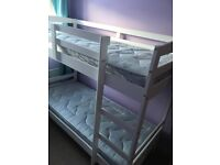 White wooden bunks with mattresses