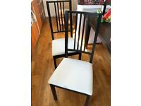 Ikea 6 wooden chairs with white cloth cushioning.