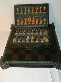 Ornate carved darkwood chessboard with mystical design chess pieces and fitted drawers