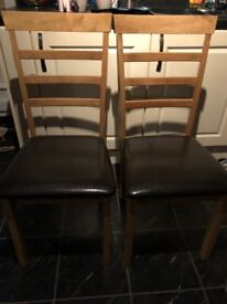 Two oak dining chairs with leather look seats