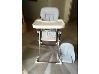 Highchair with safety harness and extra seat insert for smaller babies