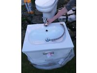 White toilet and sink with cabinet and taps
