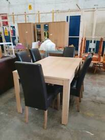 Light wood extending dining table with 6 upright faux leather chairs