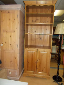 Country style pine display unit with shelving and handy storage cupboard.