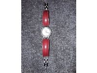 Ladies round face watch with diamanté detail around the face. Red leather strap £5