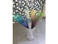 6 coloured glass champagne flutes in a vase