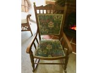 A vintage oak rocking chair with upholstered seat and back.