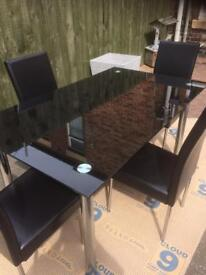 Black glass table and 4 black leather chairs .