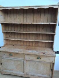 Pine kitchen dresser with sliding cupboard doors.