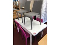 white gloss table and 4 grey and 2 pink chairs