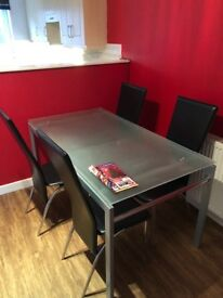 Dining room glass table 4/6 seater plus 4 black leather chairs