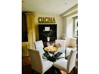 Circular glass dining table with 4 cream coloured linen chairs.