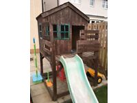 Wooden play house with slide.