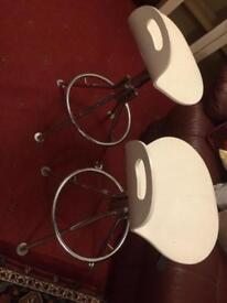 Two white bar stools with gas lift seats