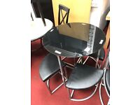 Black glass top table and 4 black chairs, space saver