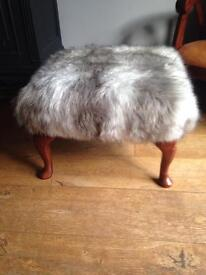 Footstool covered in grey and white throw fabric