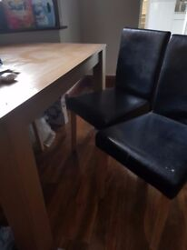 Small dining room table with four leather chairs