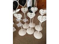 Six cream metal table name holders.