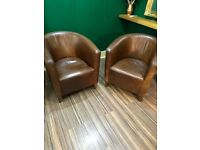 A pair of vintage leather tub chairs