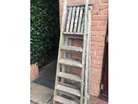 Two sets of wooden painting ladders.