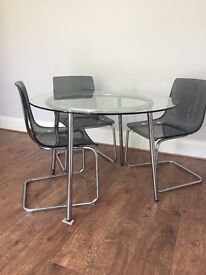 Circular glass table & 3 Chairs.